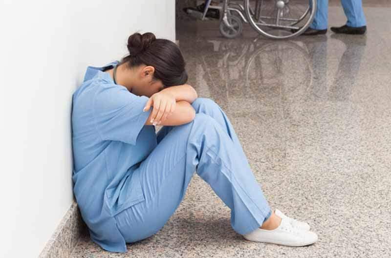 Une infirmière en pleurs dans un hôpital